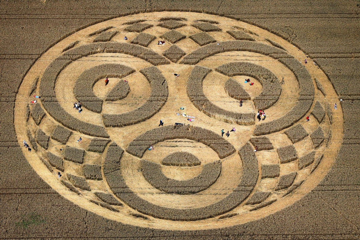 Image: People walk through crop circles shaped into a cornfield