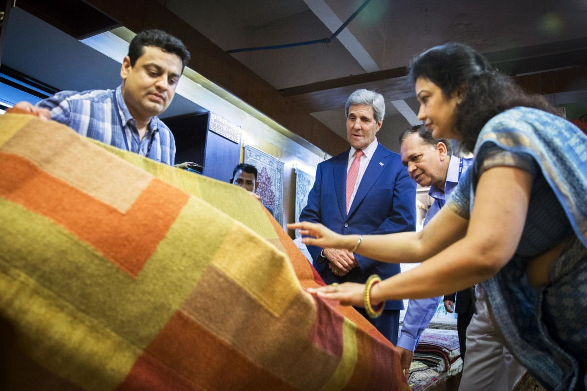 Image: U.S. Secretary of State John Kerry looks at carpets during a visit to the Central Cottage Industries Emporium marketplace