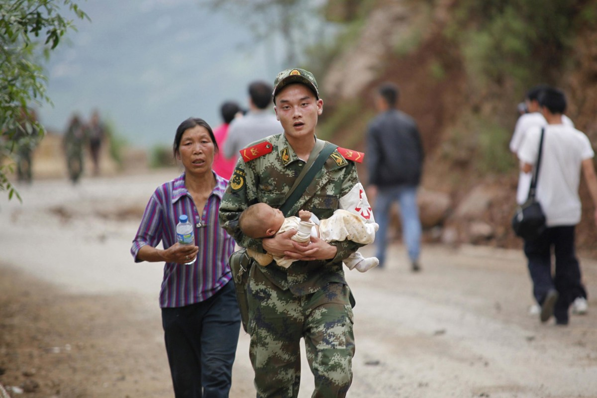 Image: A Chinese rescuer carries a baby after an earthquake hit an area in southwest China.