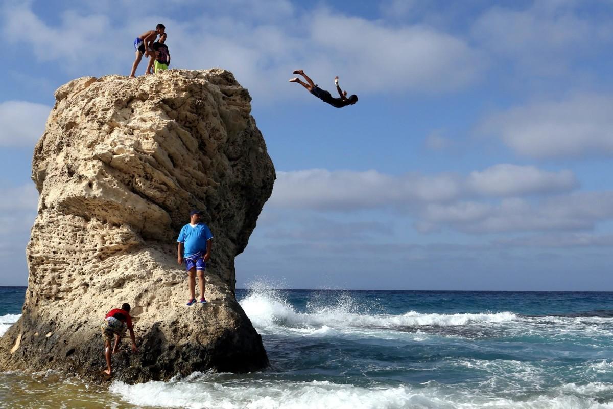 Image: An Egyptian boy dives off Lila Murad rock in Marca Matroh, Cairo