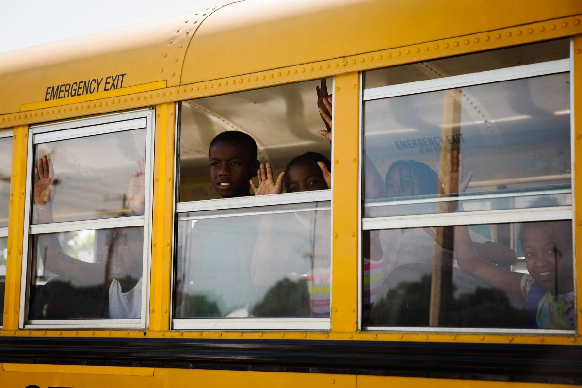 "Image: Children on a school bus gesture and chant, ""Hands up, don't shoot"""