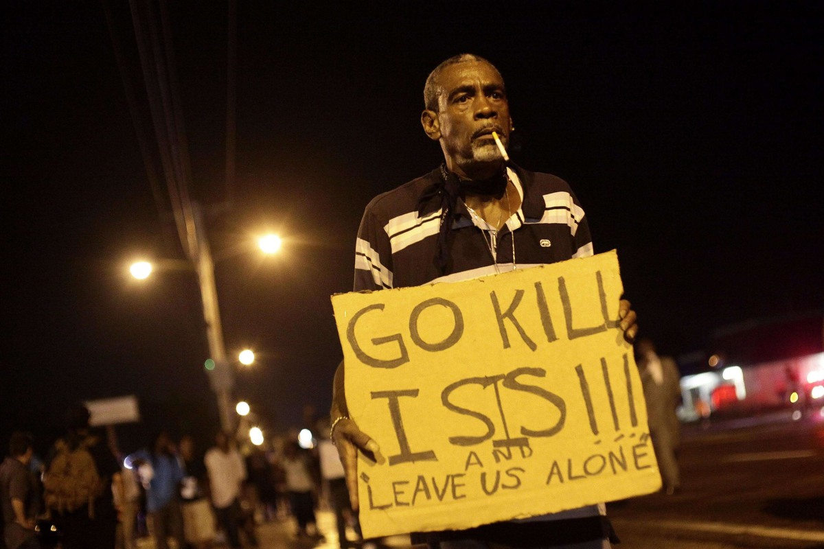 Image: A demonstrator protests the shooting death of Michael Brown