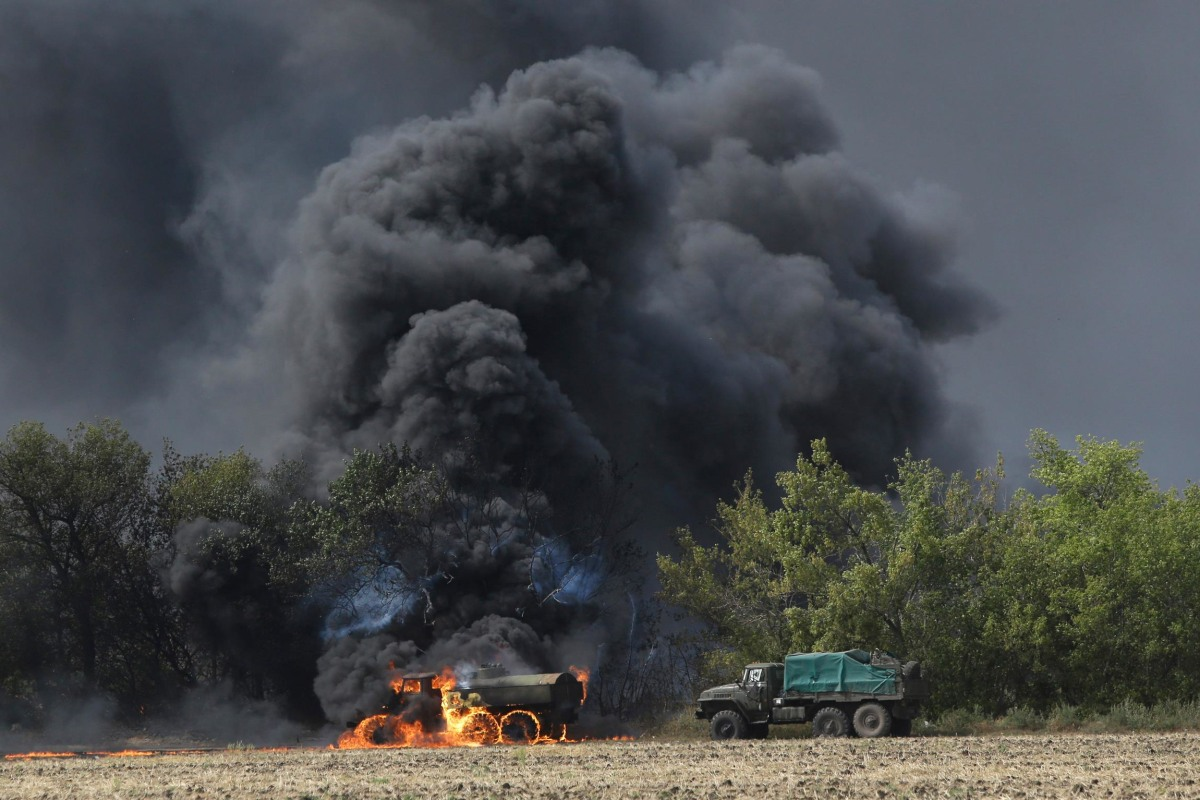 Image: An unmarked military vehicle burns on a country road in the village of Berezove, eastern Ukraine
