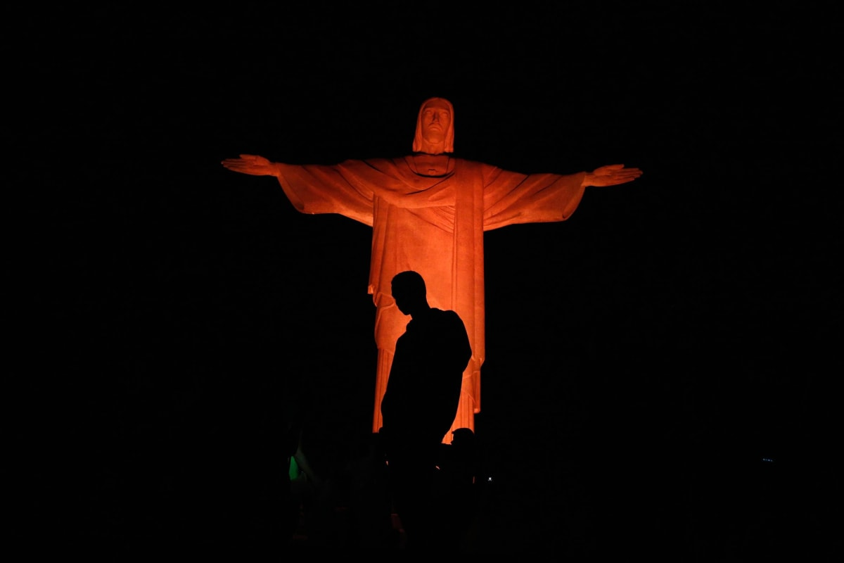 Image: Man stands in front of statue of Christ the Redeemer as it is lit up in orange to commemorate the Day against Human Trafficking and Missing Persons, celebrated by the Archdiocese of Rio de Janeiro