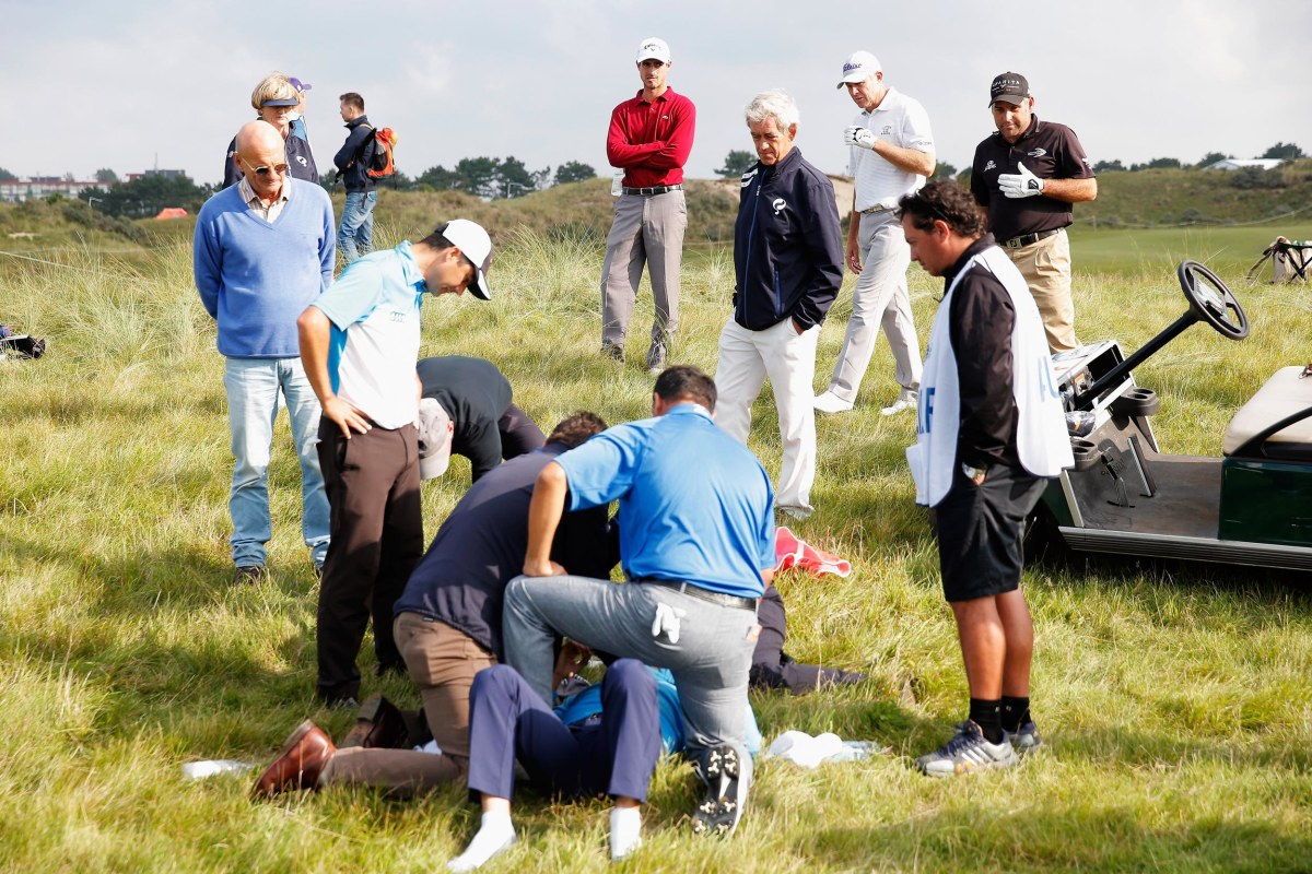 Image: Golfer Fabrizio Zanotti of Paraguay is attended to by medical staff after being struck with a ball