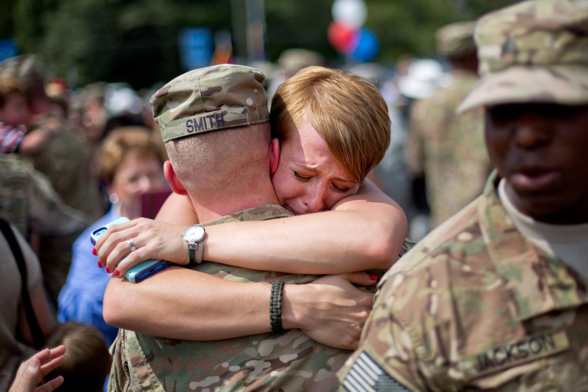 Image: Bailey Smith, right, embraces her husband Capt. Jared Smith as he returns from a deployment to Afghanistan with the Georgia National Guard's 48th Infantry Brigade Combat Team