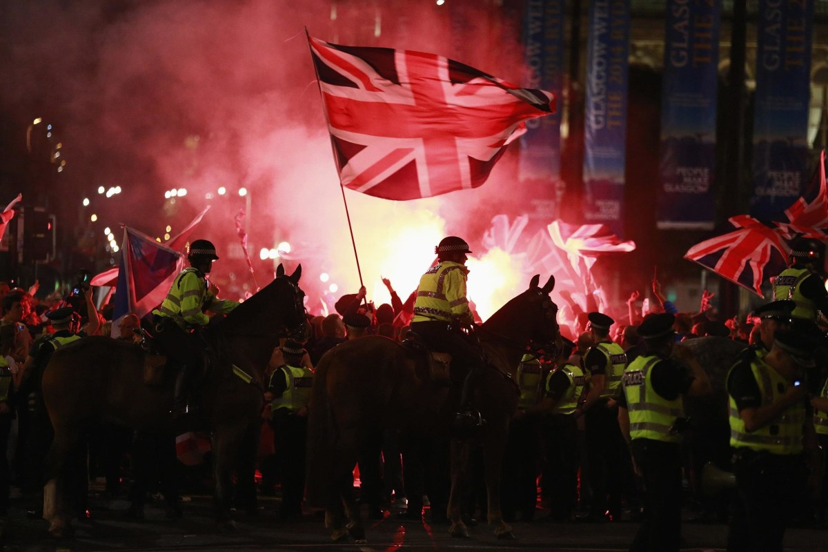 Image: Flares are let off as police stand guard while pro-union protestors clash with pro-independence protestors during a demonstration at George Square in Glasgow