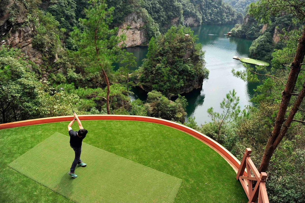 Image: Staff member plays a shot towards a putting green on a lake from a tee ground on top of a hill, at Zhangjiajie, Hunan province