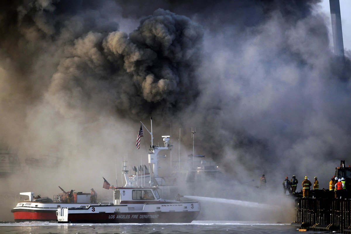 Image: Los Angeles firefighters watch as smoke from a dock fire continues to rise at the Port of Los Angeles