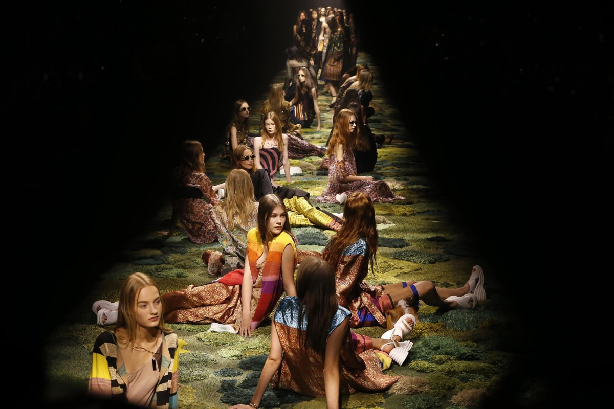 Image: Models sit on the catwalk during Dries van Noten's Spring/Summer 2015 ready-to-wear fashion collection