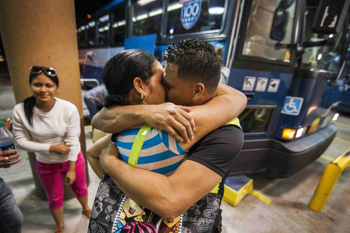 Image: Cuban migrant Mailin Perez embraces with her husband Jose Caballero (2nd L) after arriving via Mexico at a bus station in Austin