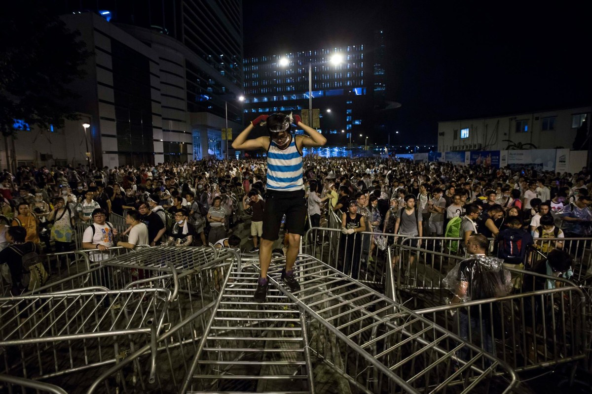 Image: A pro-democracy student stands on railings during a rally outside the government headquarters in Hong Kong