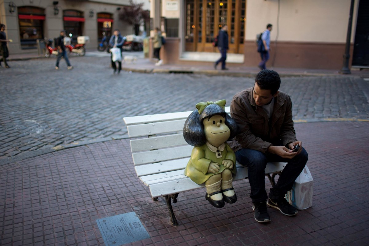 Image: A tourist sits on a bench beside the statue of comic strip characeter Mafalda