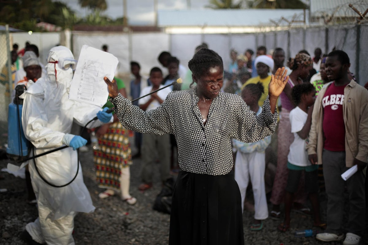 Image: A woman being discharged from the Island Clinic Ebola treatment center in Monrovia, Liberia, is sprayed with disinfectant