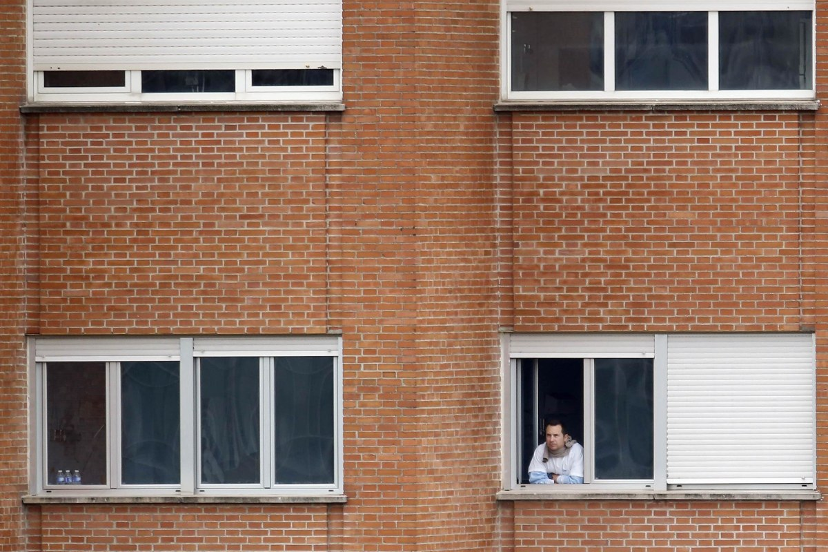 Image: Javier Limon Romero, the husband of Spanish nurse Teresa Romero Ramos who contracted Ebola, looks out of the window of a ward he is being kept isolated in, at Madrid's Carlos III hospital