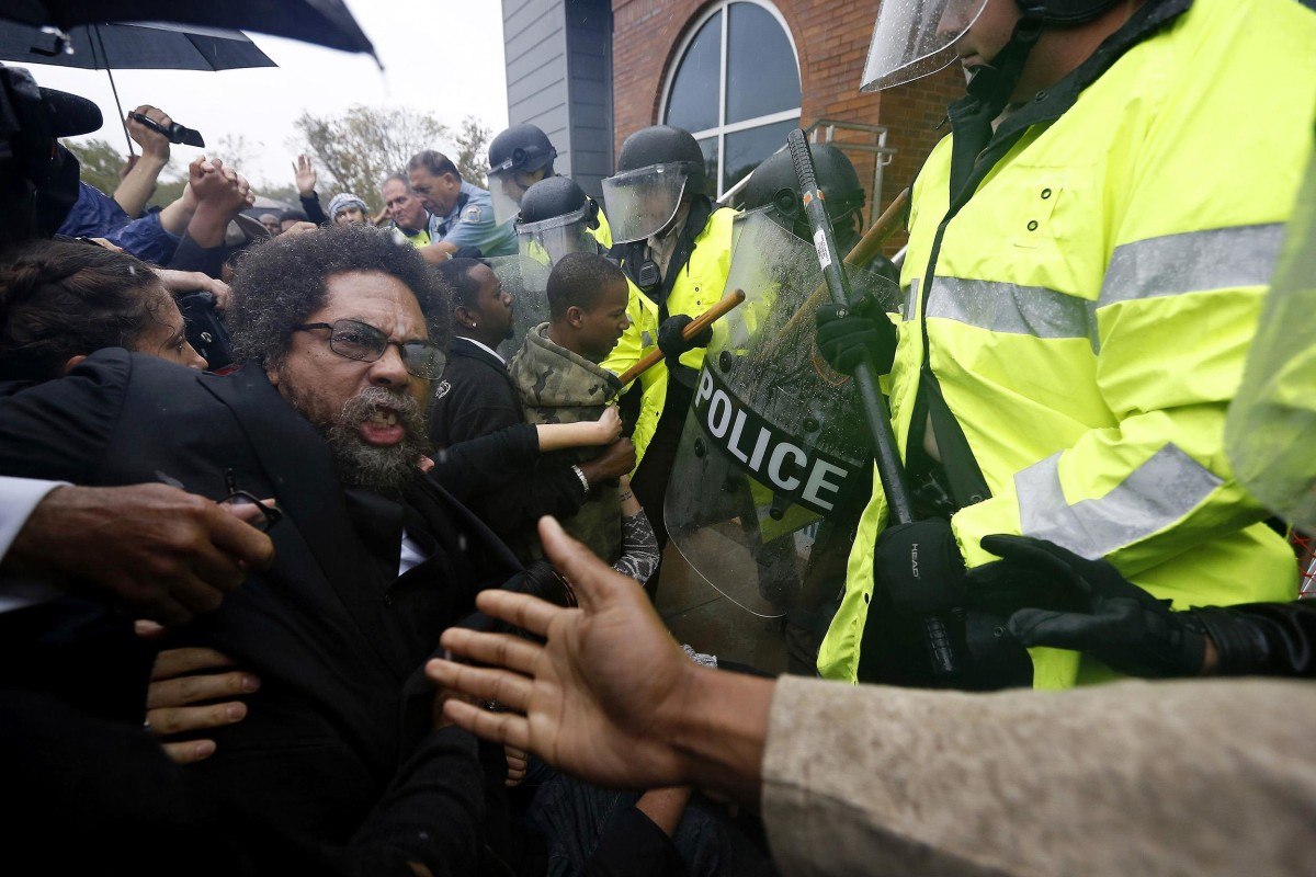Image: Activist Cornel West is knocked over during a scuffle with police during a protest at the Ferguson Police Department in Ferguson