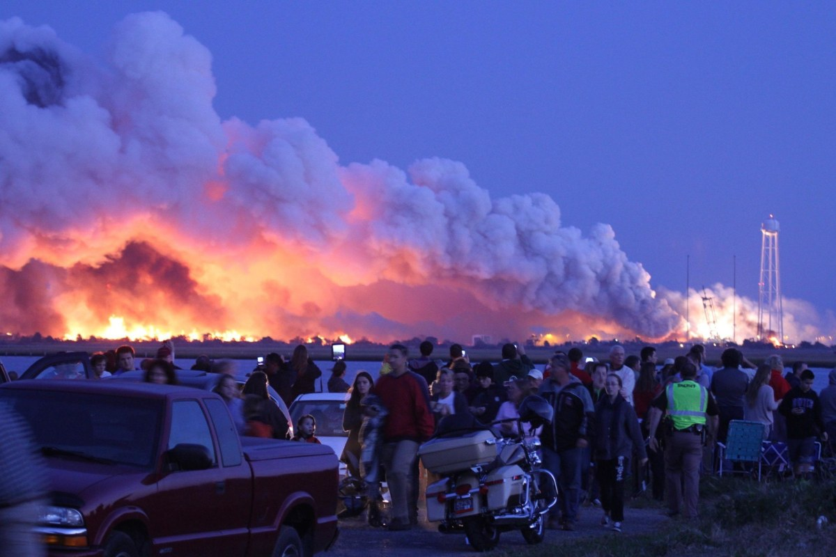 Image: People who came to watch the launch walk away after an unmanned rocket owned by Orbital Sciences Corporation exploded