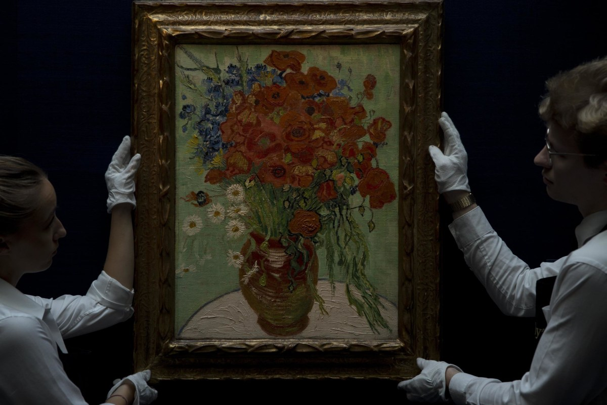 Sotheby's employees stand next to painting by Vincent Van Gogh, said to be on of his last, entitled 'Still Life- Vase with Daisies and Poppies' 1890.