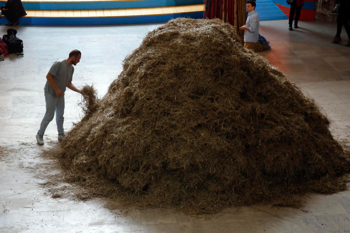 "Image: Italian artist Sven Sachsalber starts to search a needle hidden in a haystack during an art performance based on the expression ""looking for a needle in a haystack"" at the Palais de Tokyo museum in Paris"