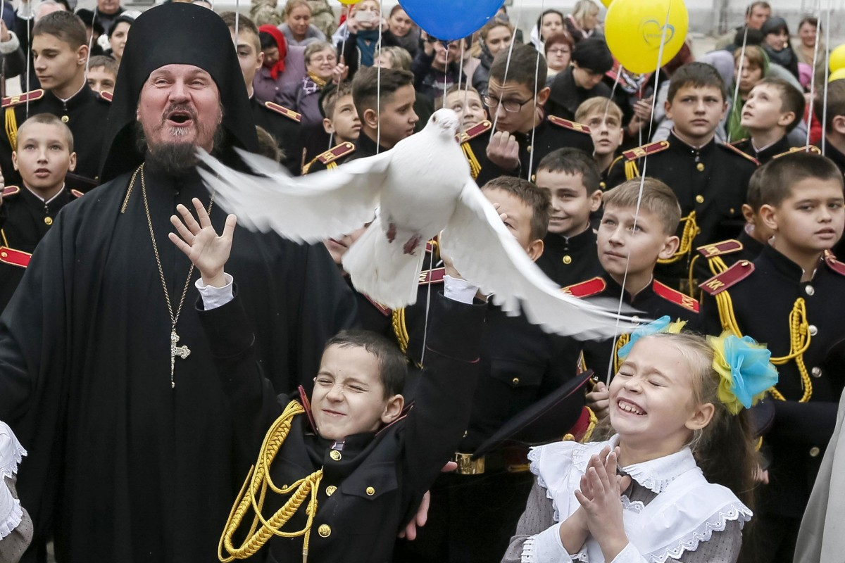 Image: A young military cadet releases a pigeon after an oath-taking ceremony at the Kiev Pechersk Lavra monastery in Kiev