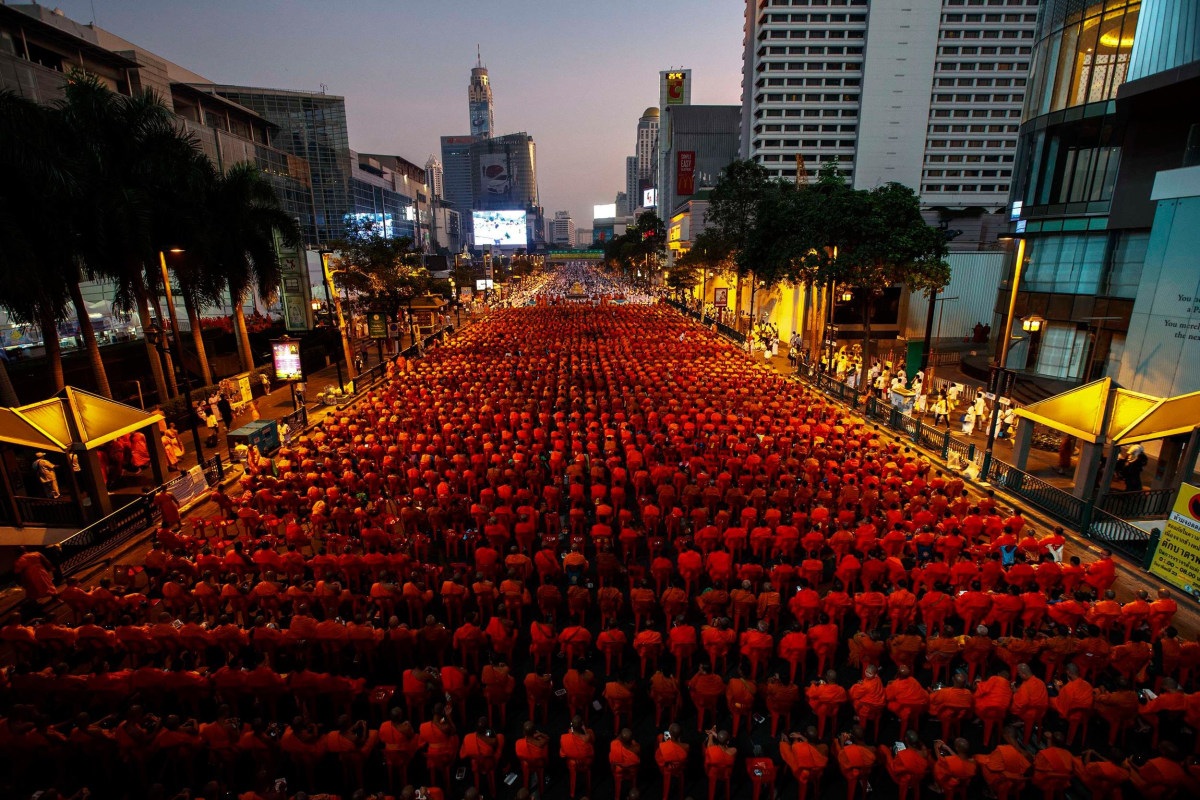 Image: Thousands of Buddhist monks attend a mass alms-offering ceremony in Bangkok's shopping district