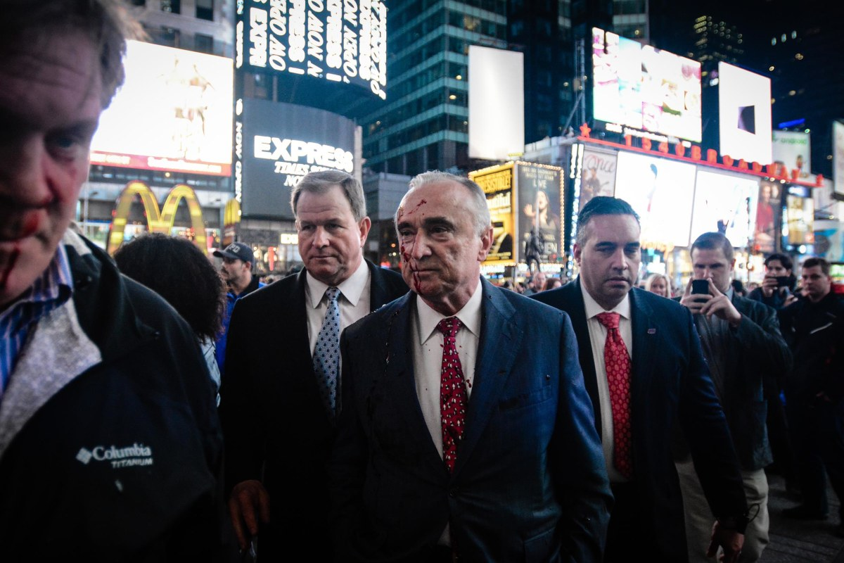 A protester threw fake blood on NYPD Commissioner Bill Bratton during a demonstration over the death of Michael Brown in New York's Times Square on Monday night.