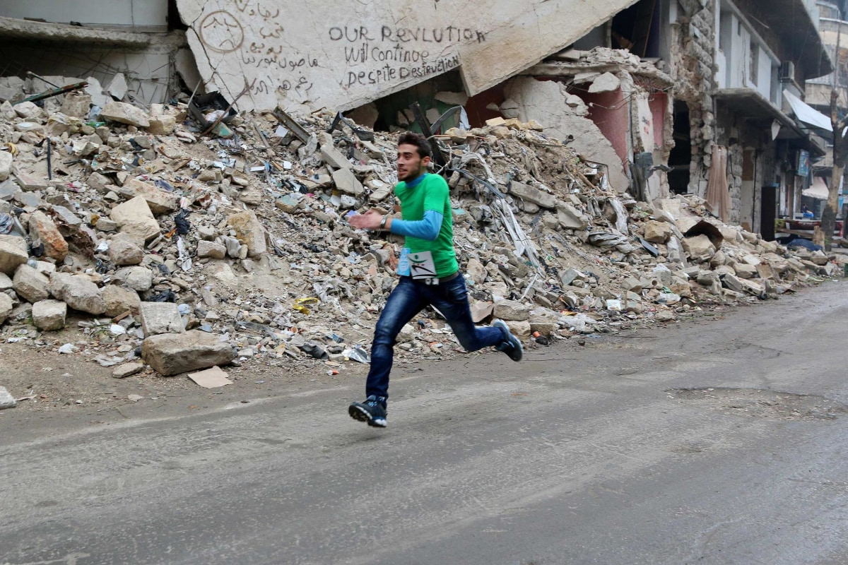 Image: A participant runs past a damaged building as he competes in a running race along a street in Aleppo's Bustan al-Qasr neighborhood