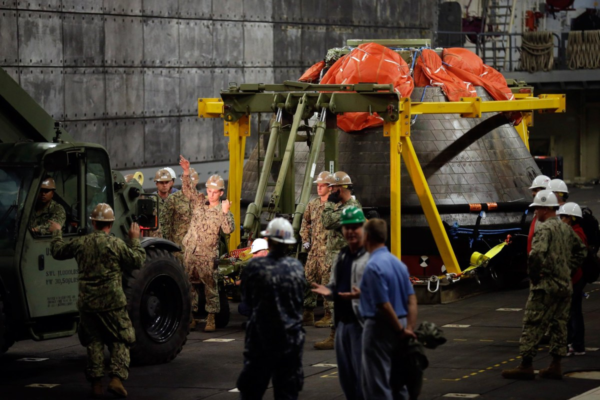 Image: Navy personnel work as NASA's Orion space capsule is prepared to be unloaded from the USS Anchorage