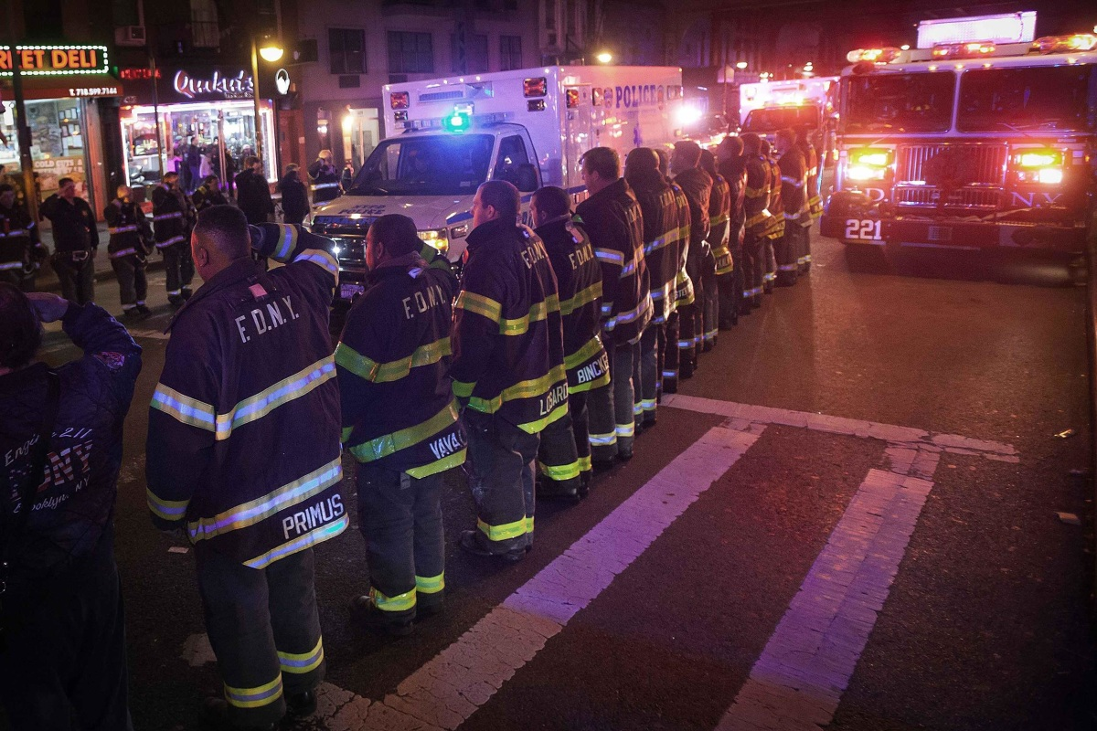 Image: An ambulance carrying one of the two New York Police officers who were shot dead passes by a New York Fire Department honor guard along Broadway in the Brooklyn borough of New York