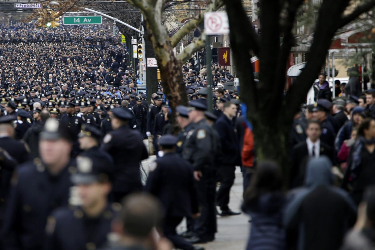 Image: Police officers line the streets before the funeral of Officer Wenjian Liu in the Brooklyn borough of New York, Sunday, Jan. 4. Liu and his partner, officer Rafael Ramos, were killed Dec. 20 as they sat in their patrol car on a Brooklyn stree