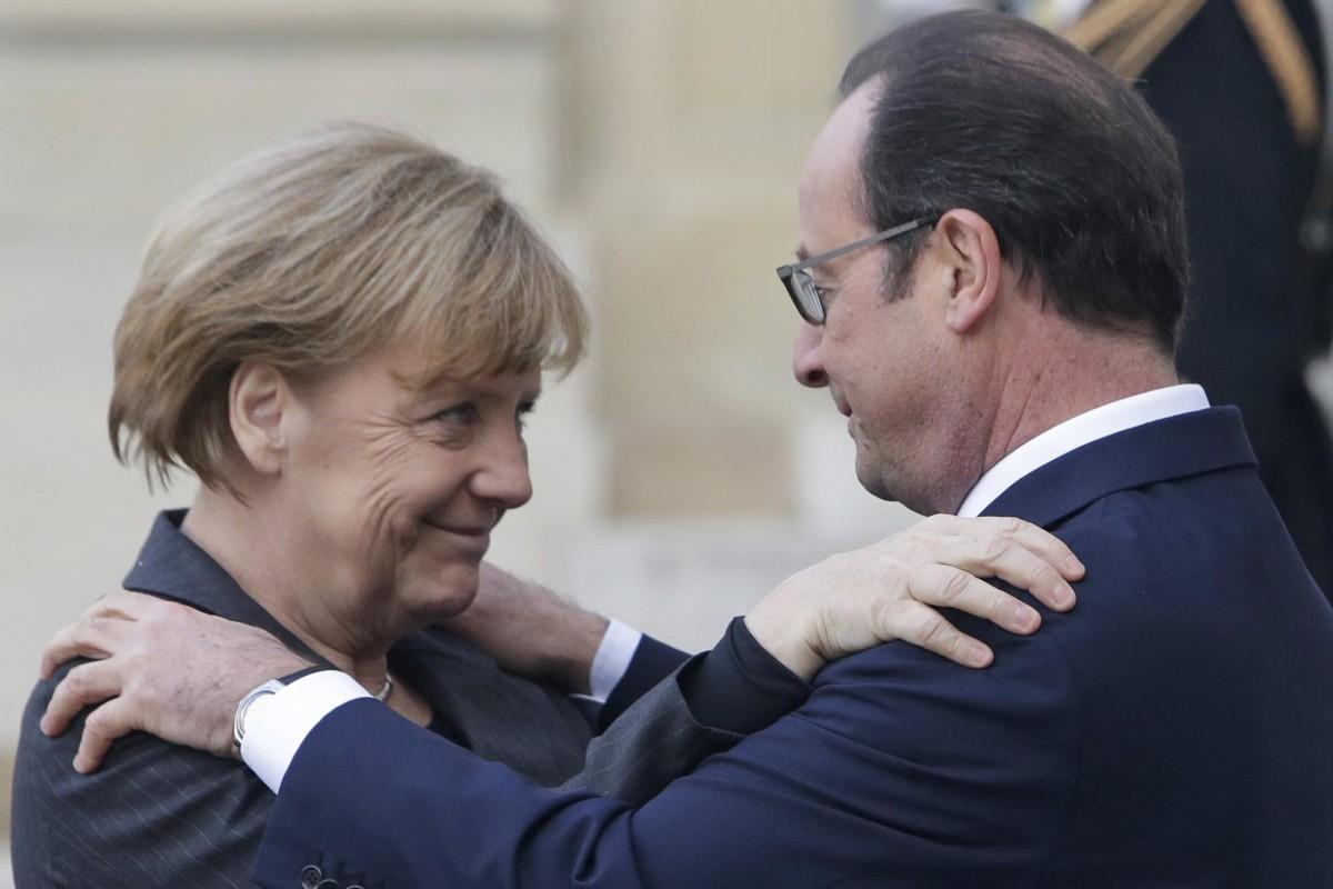 Image: French President Francois Hollande embraces German Chancellor Angela Merkel, left, as she arrives at the Elysee Palace, Paris, Sunday, Jan. 11, 2015