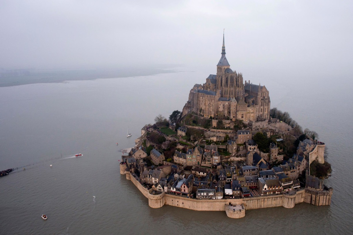 Image: An aerial view as a high tide submerges a narrow causeway leading to the Mont Saint-Michel