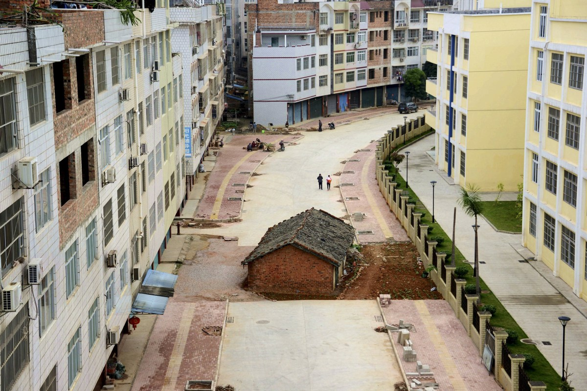 """Image: A """"nail house"""", the last building in the area, sits in the middle of a road under construction in Nanning"""
