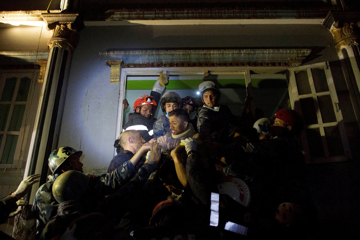 Image: Khanal, an injured survivor is taken out by French rescue teams from a damaged building following Saturday's earthquake in Kathmandu