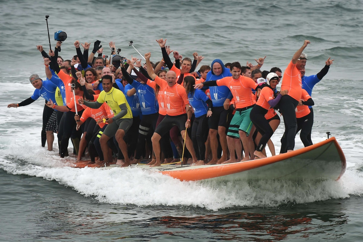 Image: Sixty six surfers from Huntington Beach ride the world's largest surfboard