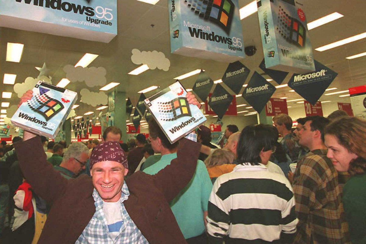 Image: Mikol Furneaux waves two packages of Windows 95 software in the first store in Australia to sell the product