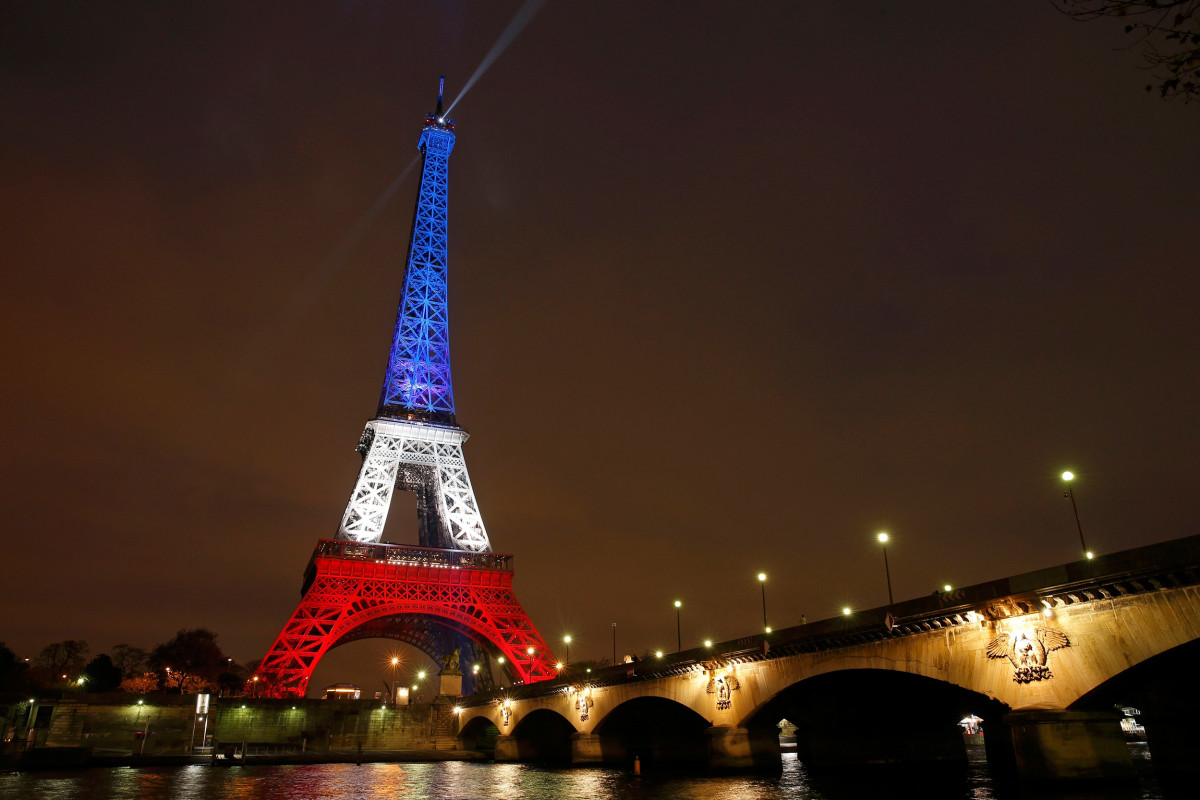 Image: The Eiffel Tower is lit with the blue, white and red colours of the French flag in Paris to pay tribute to the victims of a series of deadly attacks in the French capital