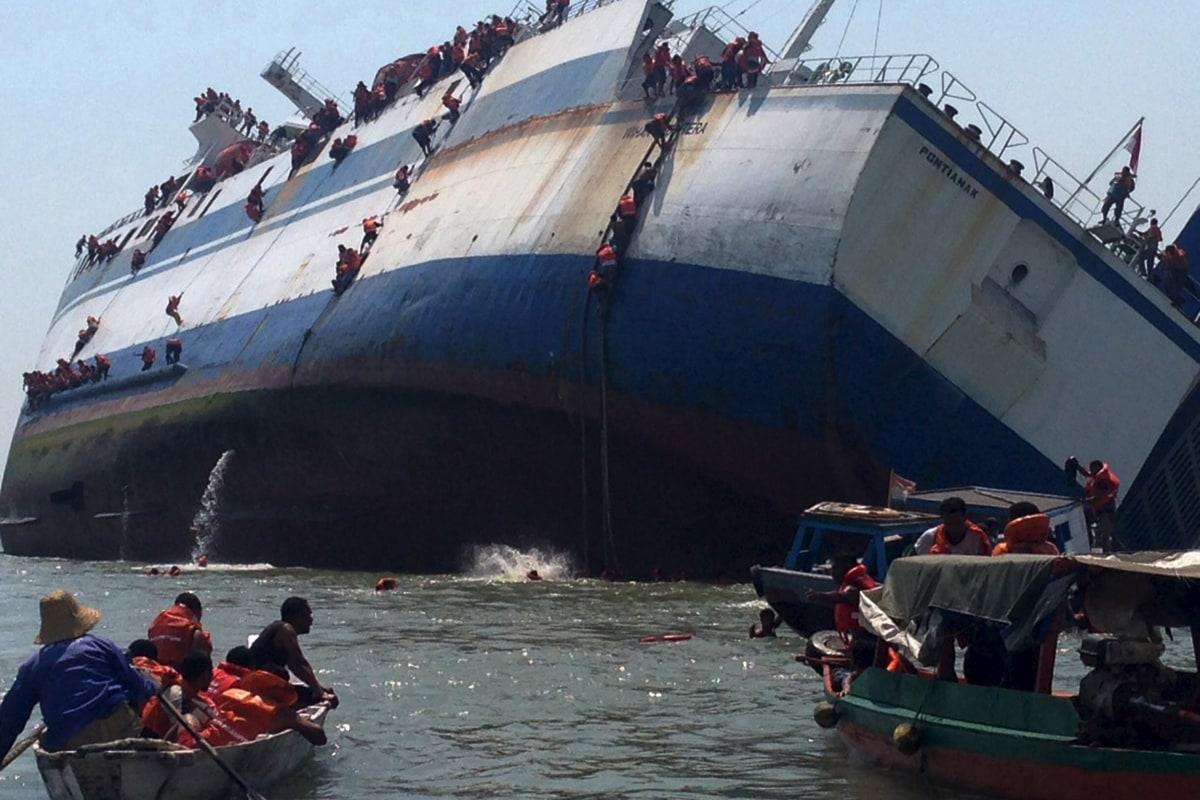 Image: Passengers climb down the side of the ferry KM Wihan Sejahtera as it capsizes in Tanjung Perak port, Surabaya