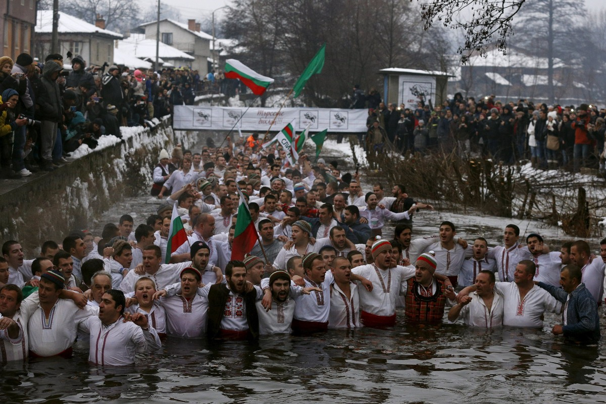 Image: Bulgarian men dance in the icy waters of the Tundzha river