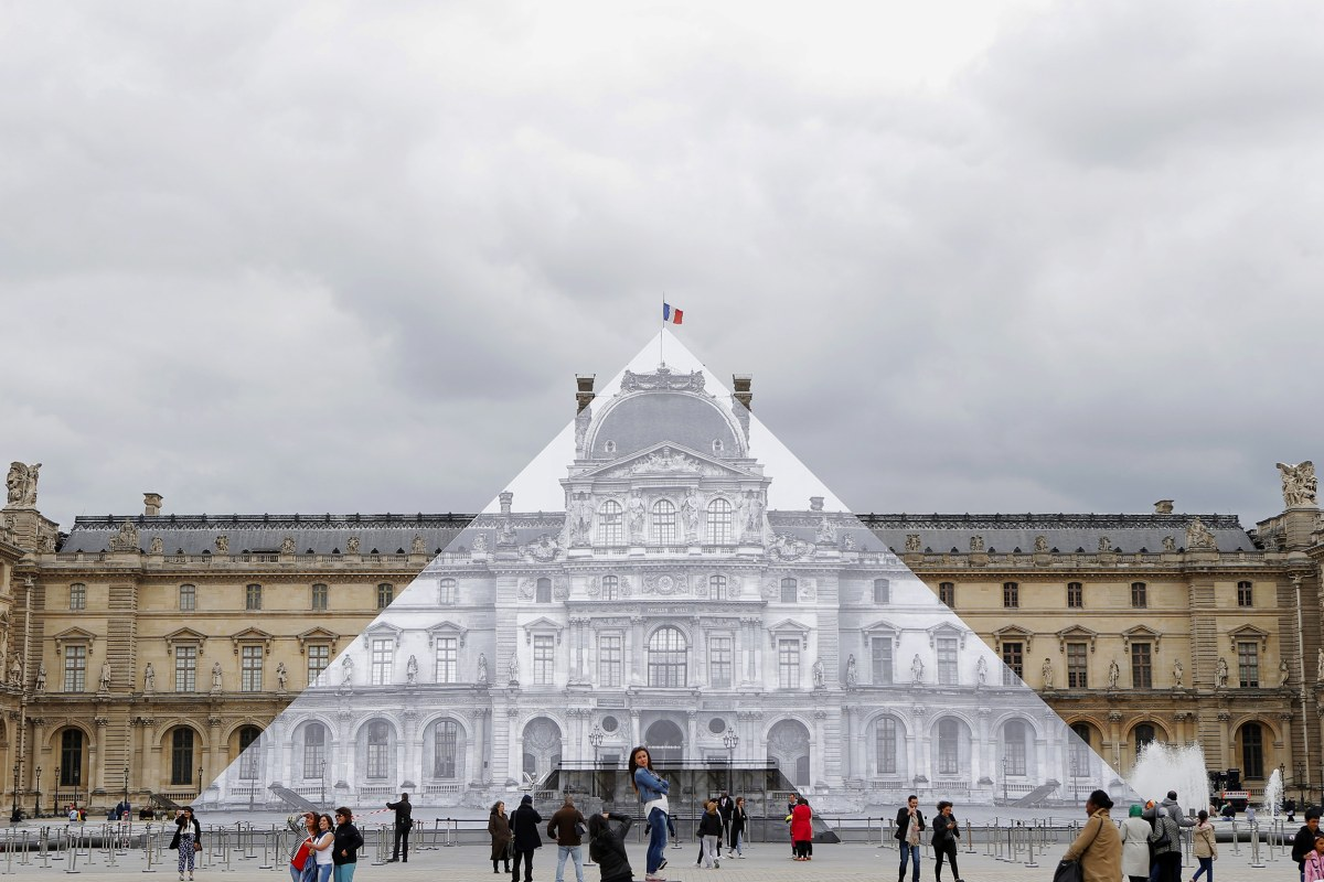 Image: Tourists walk around the JR project at the Louvre Pyramid