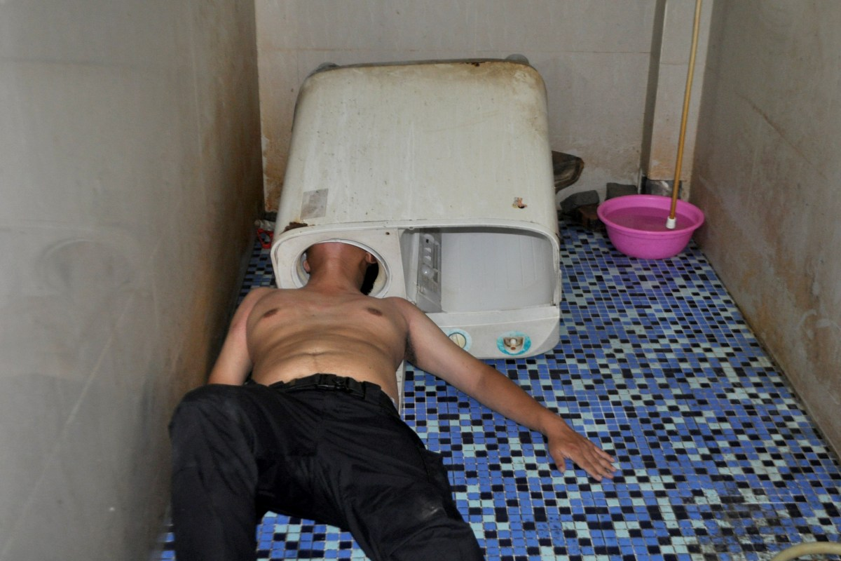 Image: A man lies on the ground as his head is stuck in a washing machine in Fuqing county of Fuzhou