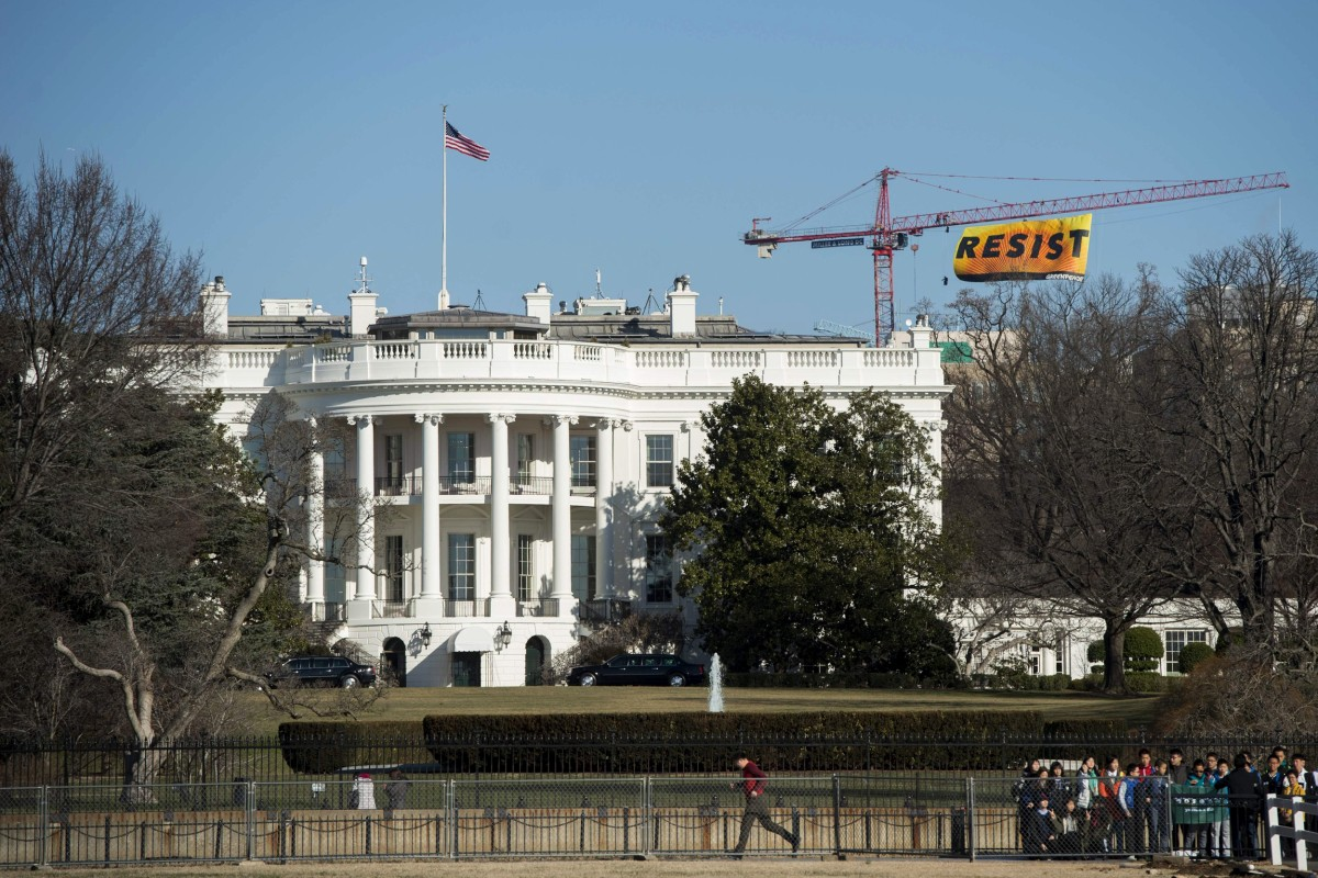 """Image: Greenpeace protesters unfold a banner reading """"Resist"""" from atop a construction crane behind the White House on Jan. 25, 2017 in Washington, D.C."""