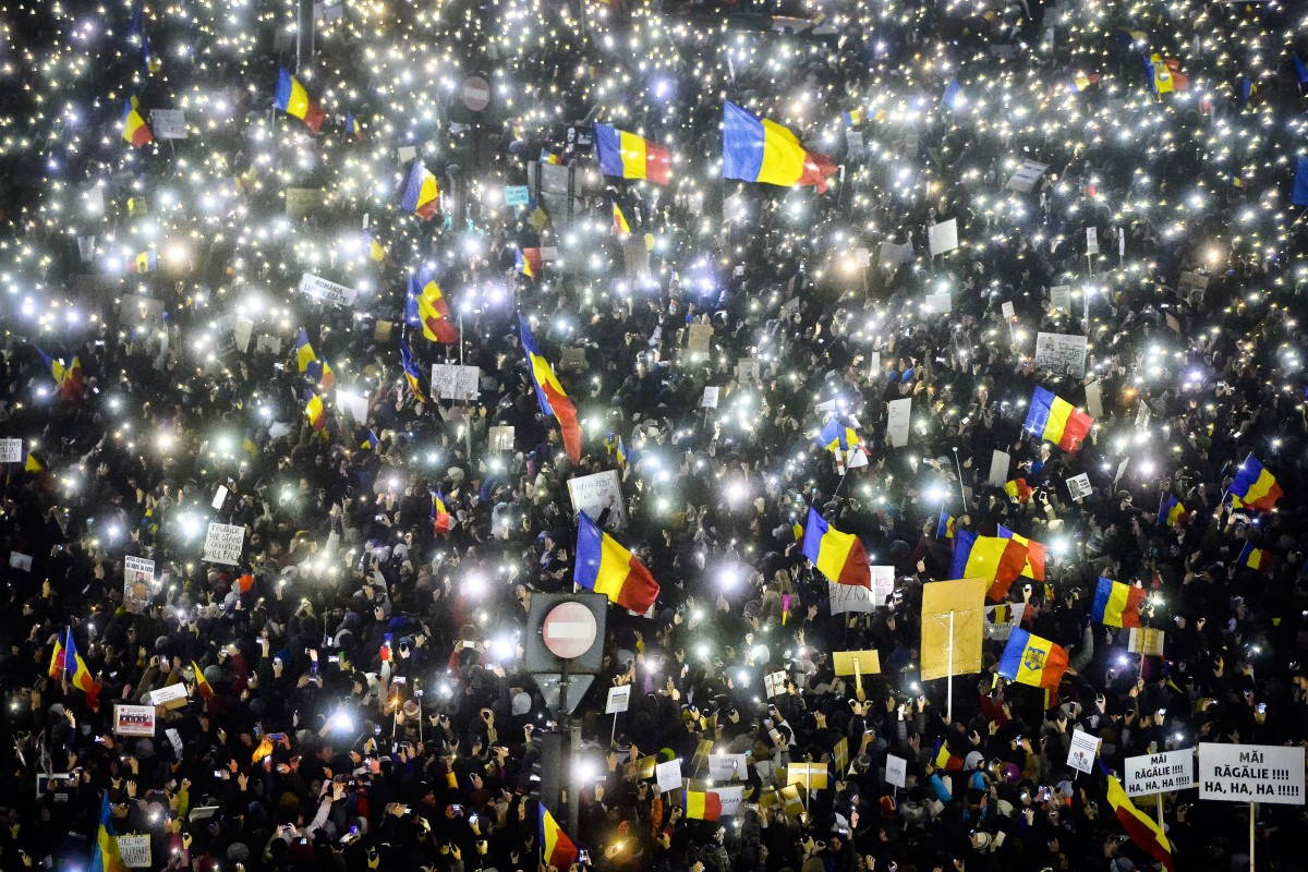Image: Tens of thousands of people shine lights in front of the government building in Bucharest, Sunday.