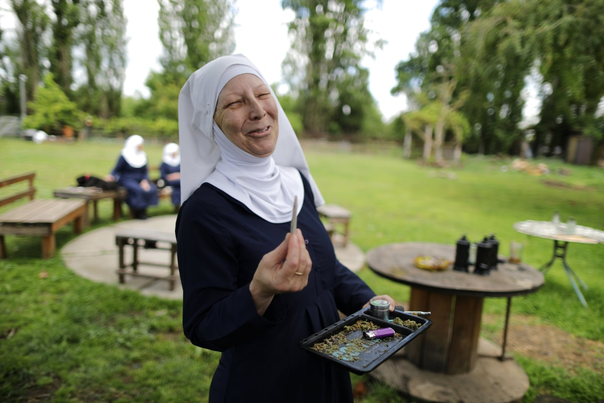 """Image: California """"weed nun"""" Christine Meeusen, lights a joint at Sisters of the Valley near Merced"""