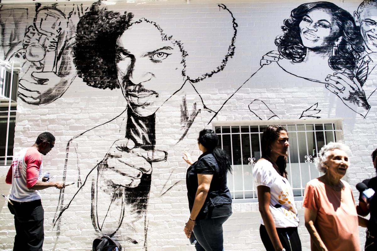 Image: Muralist Aniekan Udofia, left, works on his new mural