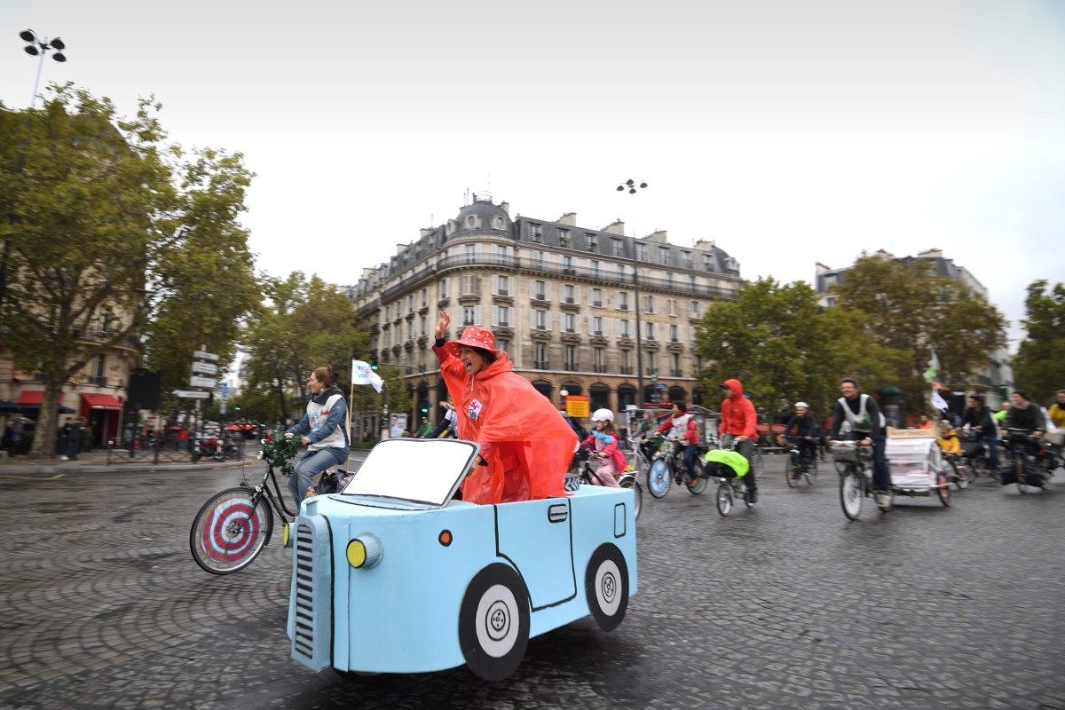 "Image: A woman rides a cardboard car on Place de la Bastille during a ""car free"" day in Paris"