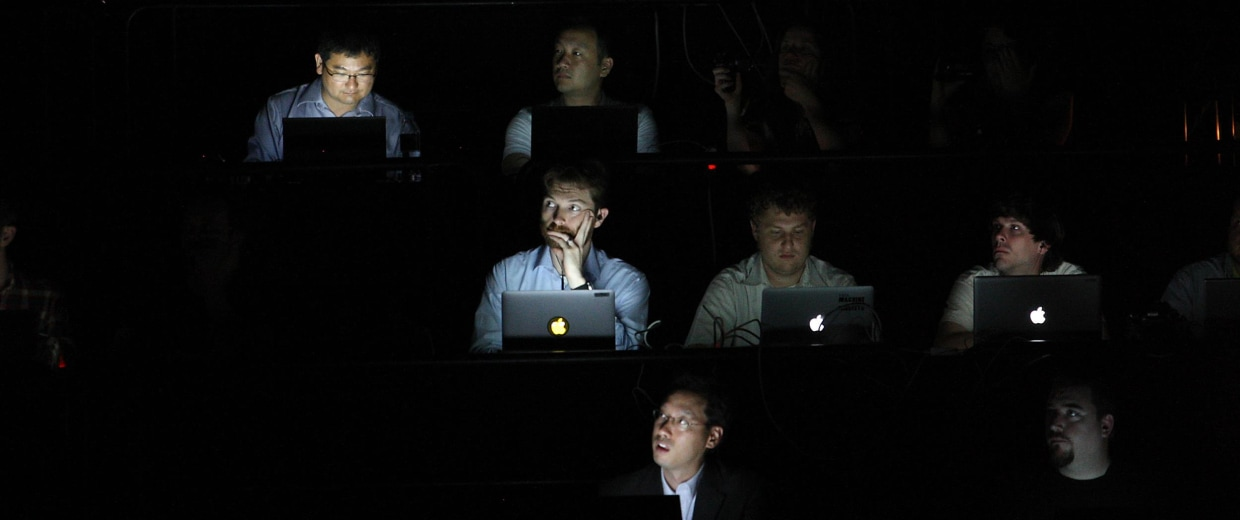 Image: People in the audience are illuminated by the screens of their laptop computers.