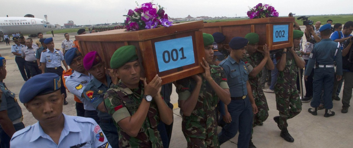 Image: Indonesian military carry the caskets containing the bodies of two AirAsia flight QZ8501 passengers recovered off the coast of Borneo at a military base in Surabaya