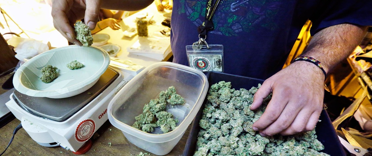 Image: An employee weighs portions of retail marijuana to be packaged and sold at 3D Cannabis Center in Denver.
