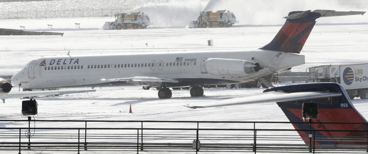 Image: Plows clear snow from a runway at JFK Airport in New York on Friday.